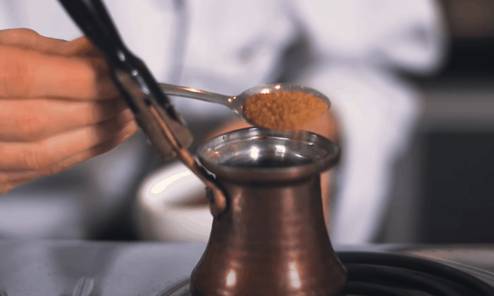 If you're using sugar andor cardamom, mix it with the ground coffee